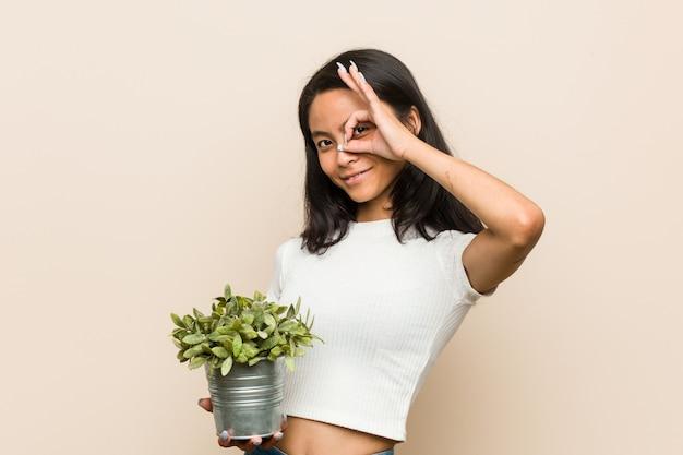 La giovane donna asiatica che tiene una pianta ha eccitato mantenendo il gesto giusto sull'occhio.