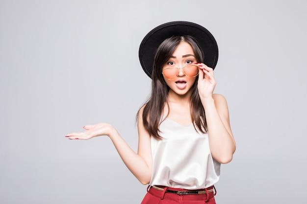 La giovane donna asiatica con gli occhiali da sole gesture con le mani isolate sulla parete bianca