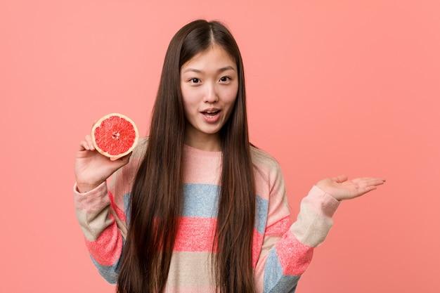 La giovane donna asiatica con un pompelmo ha impressionato lo spazio della copia della tenuta sulla palma.