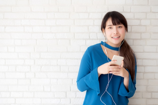 La giovane donna asiatica del bello ritratto che sta felice gode e si diverte ascolta musica con la cuffia