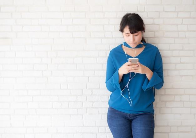 La giovane donna asiatica del bello ritratto che sta felice gode e si diverte ascolta musica