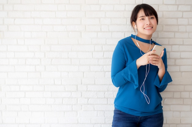 La giovane donna asiatica del bello ritratto che sta felice gode e si diverte