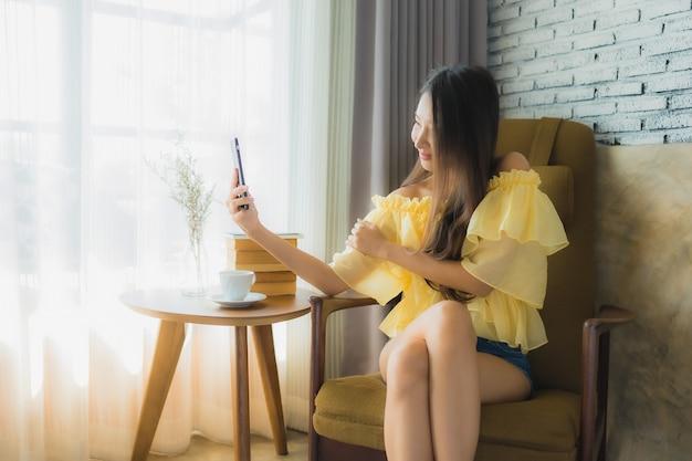 La giovane donna asiatica del ritratto che utilizza il telefono cellulare con la tazza di caffè ed il libro letto si siedono sulla sedia nel salone