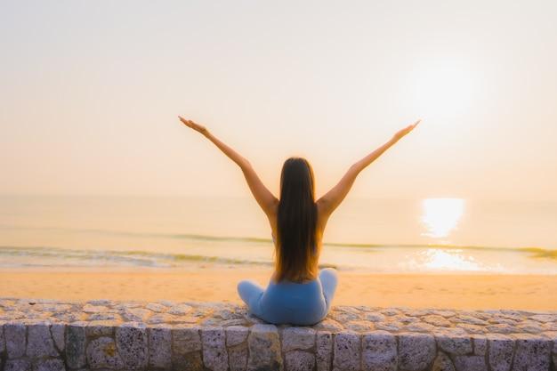 La giovane donna asiatica del ritratto fa la meditazione intorno all'oceano della spiaggia del mare all'alba