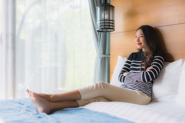 La giovane donna asiatica del ritratto felice si rilassa il sorriso sulla decorazione del letto in camera da letto