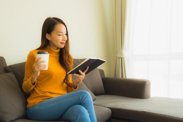 La giovane donna asiatica del ritratto ha letto il libro sulla sedia del sofà con il cuscino in salone