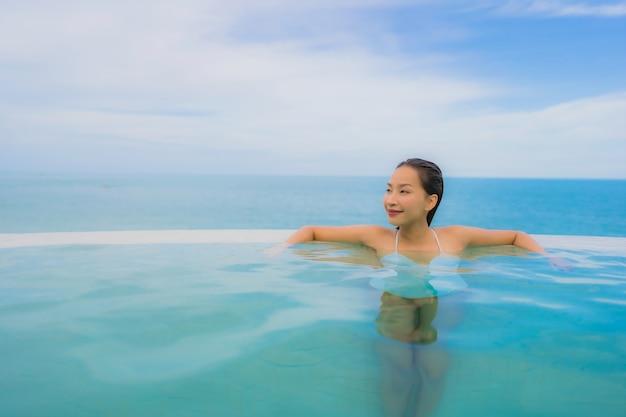 La giovane donna asiatica del ritratto si rilassa il sorriso felice intorno alla piscina all'aperto nella località di soggiorno dell'hotel con la vista di oceano del mare
