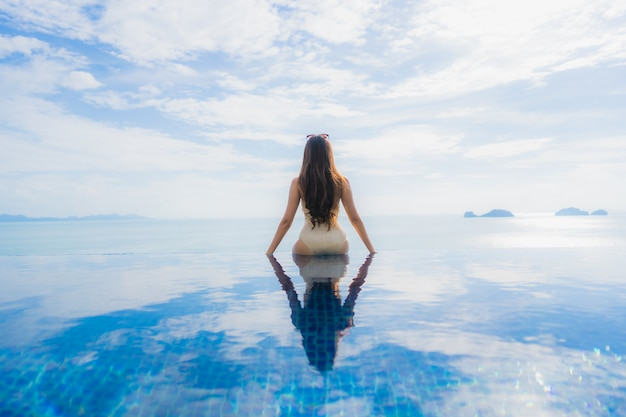 La giovane donna asiatica del ritratto si rilassa il sorriso felice intorno alla piscina in hotel e ricorso