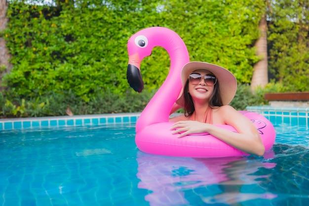 La giovane donna asiatica del ritratto si rilassa il sorriso felice intorno alla piscina in hotel