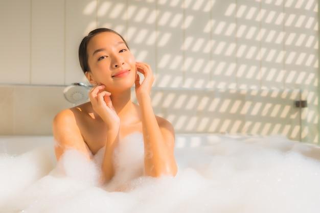La giovane donna asiatica del ritratto si rilassa prende un bagno in vasca