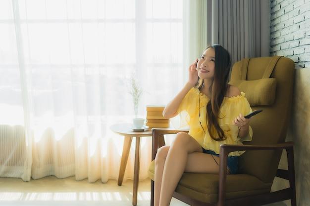 La giovane donna asiatica del ritratto si siede sulla sedia ascolta musica con il caffè e il libro del telefono cellulare