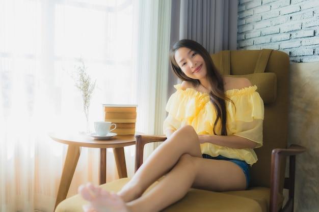 La giovane donna asiatica del ritratto si siede sulla sedia del sofà e legge il libro con la tazza di caffè