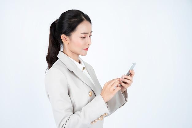 La giovane donna asiatica di affari in abito grigio, è intelligente e sicura di sé. il manager sta pensando al lavoro e all'uso del telefono.
