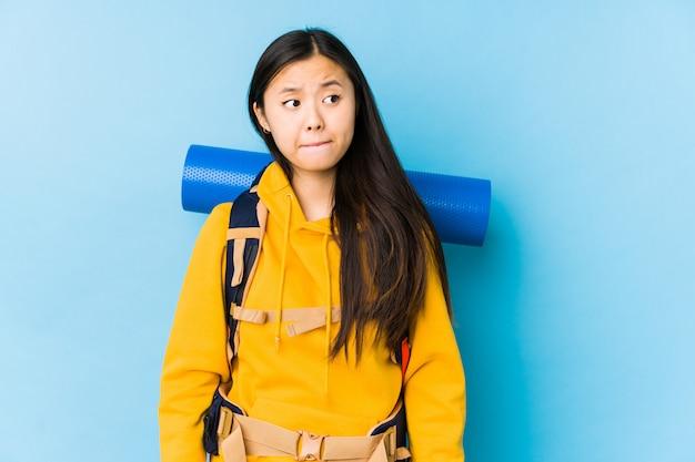 La giovane donna asiatica di viaggiatore con zaino e sacco a pelo confusa, si sente dubbiosa e incerta