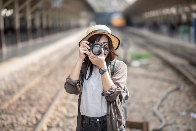 La giovane donna asiatica di viaggio sta godendo con il bellissimo posto a bangkok