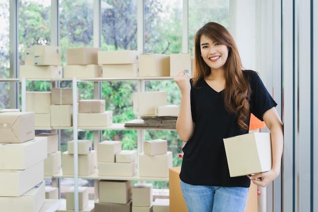 La giovane donna asiatica felice di affari è porta una scatola del pacchetto che imballa e che mostra il successo di affari