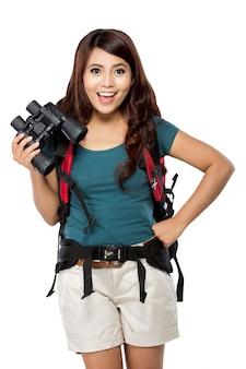 La giovane donna asiatica ha con un knapshack e un binocolo