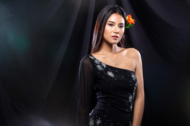 La giovane donna asiatica indossa un abito da sera con paillettes