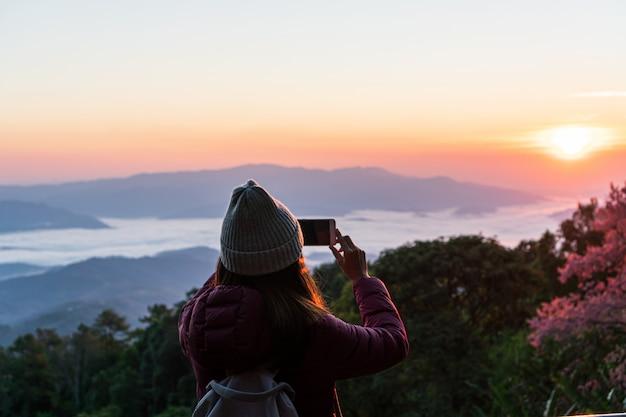 La giovane donna asiatica prende una foto alla bella alba e al cielo variopinto nella foschia sopra la montagna