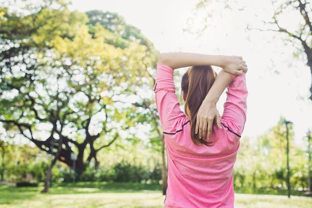 La giovane donna asiatica riscalda il corpo che si allunga prima di mattina si esercita e yoga nel parco