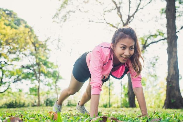 La giovane donna asiatica riscalda il suo corpo spingendo su per sviluppare la sua forza