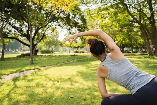 La giovane donna asiatica sana del corridore riscalda il corpo che allunga prima dell'esercitazione e dello yoga