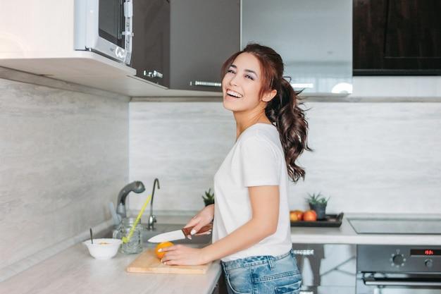 La giovane donna asiatica sorridente felice della bella ragazza dei capelli lunghi taglia il limone nella sua cucina