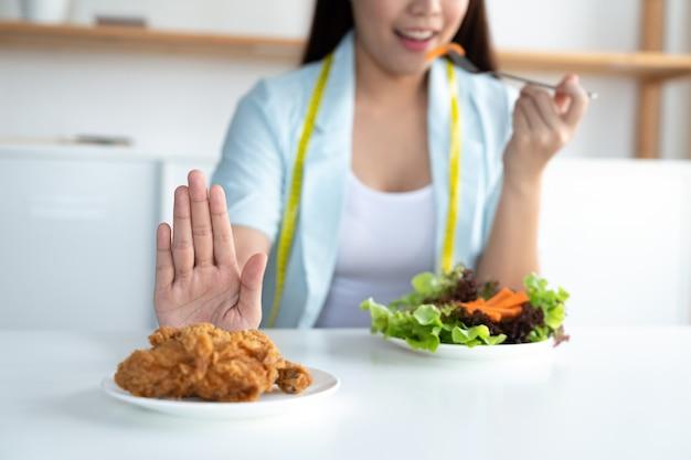 La giovane donna asiatica sulla dieta e sulla scelta mangia l'insalata di verdure dal pollo fritto dei rifiuti industriali, stante a dieta e concetto di buona salute