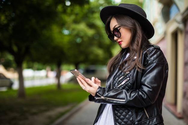 La giovane donna asiatica utilizza lo smart phone sulla via