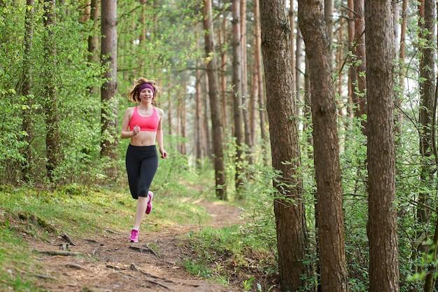 La giovane donna atletica in scarpe da tennis rosa funziona nella foresta di primavera