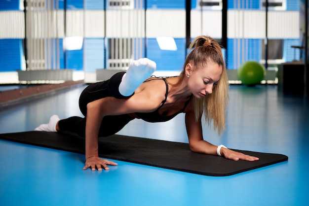 La giovane donna atletica sta preparandosi in palestra.