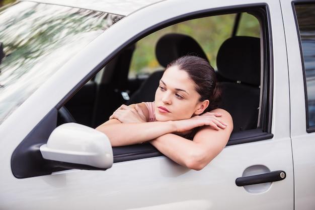 La giovane donna attende assistenza vicino alla sua auto, che si è rotta sul lato della strada