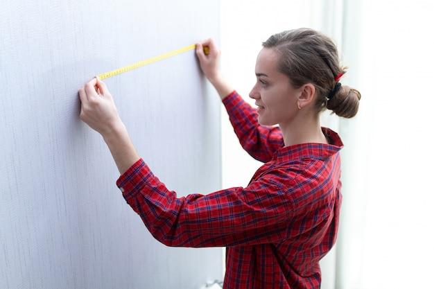 La giovane donna attraente in maglietta è impegnata in riparazioni domestiche e misura la lunghezza del muro con metro a nastro