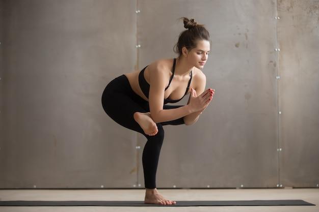 La giovane donna attraente in una posa fornita di gambe della sedia, studio grigio