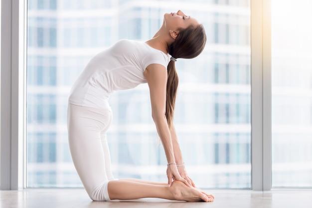 La giovane donna attraente in ustrasana posa contro il pavimento