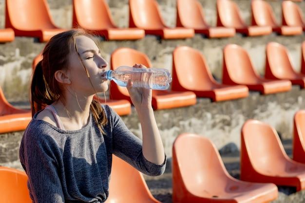 La giovane donna attraente sportiva in abiti sportivi che si rilassano dopo l'allenamento duro si siede e beve l'acqua dalla bottiglia di sport speciale dopo avere corso su uno stadio