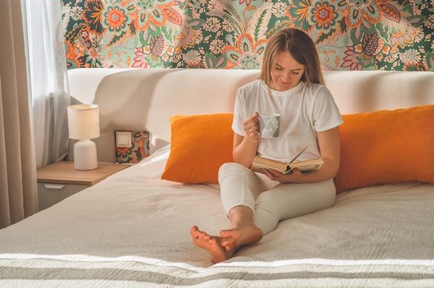 La giovane donna attraente sta leggendo un libro a casa