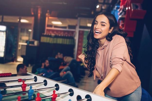 La giovane donna attraente sta nel gioco della stanza e gioca a calcio-balilla. lei sorride modello tenere la mano sul braccio giocando. lei sembra felice. gli uomini dietro si siedono.