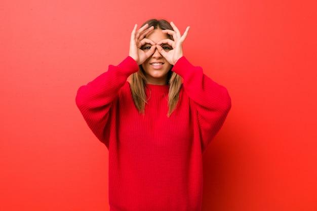La giovane donna autentica carismatica reale della gente contro una parete che mostra bene firma sopra gli occhi