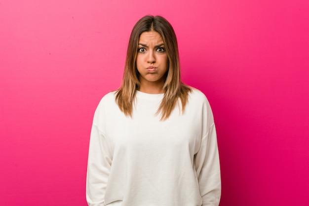 La giovane donna autentica carismatica vera gente contro un muro soffia sulle guance, ha un'espressione stanca. concetto di espressione facciale.