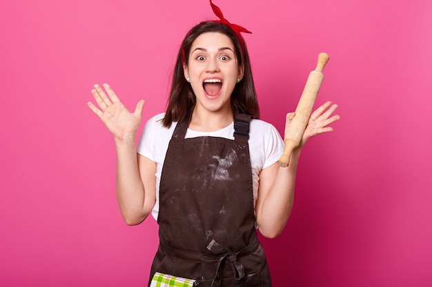 La giovane donna baker alza le mani tenendo il mattarello, indossa un grembiule marrone, una maglietta bianca, apre la bocca ampiamente. adorabile donna carina è di buon umore mentre cucina nuovi piatti. concetto di cuoco.