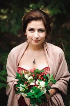 La giovane donna bellissima in un abito da sposa con un bouquet