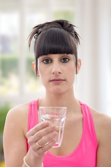 La giovane donna beve il bicchiere d'acqua