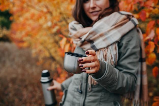 La giovane donna beve il tè nella foresta di autunno