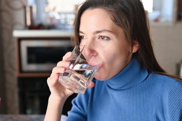 La giovane donna beve l'acqua da un bicchiere