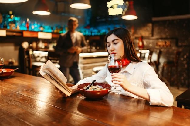 La giovane donna beve vino rosso e legge un libro al bancone del bar in legno. cliente femminile che si distende nel pub