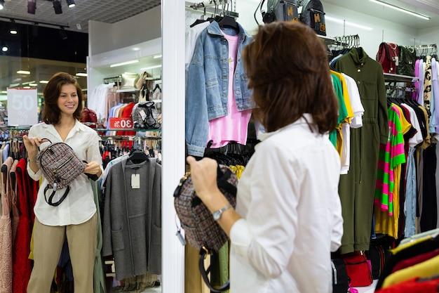La giovane donna bianca si guarda allo specchio con se stessa con la borsa in mano