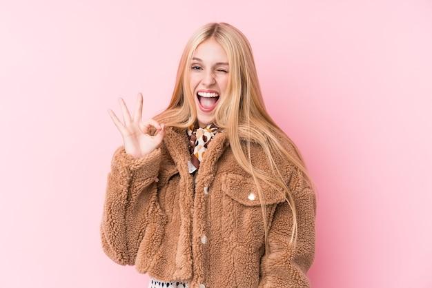 La giovane donna bionda che indossa un cappotto contro un muro rosa strizza l'occhio e tiene un gesto giusto con la mano.