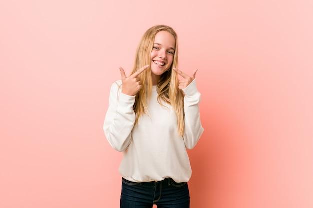 La giovane donna bionda dell'adolescente sorride, indicando le dita alla bocca.
