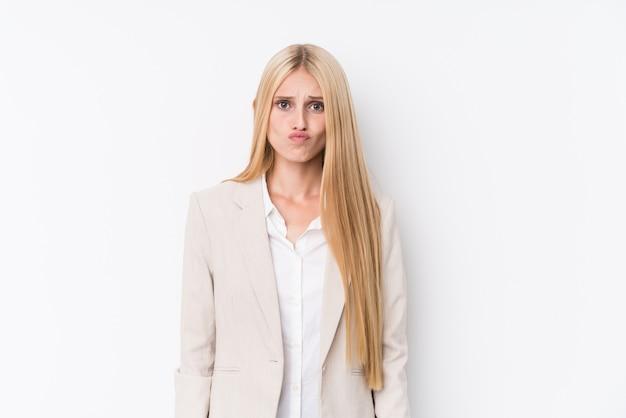 La giovane donna bionda di affari su bianco soffia le guance, ha espressione stanca